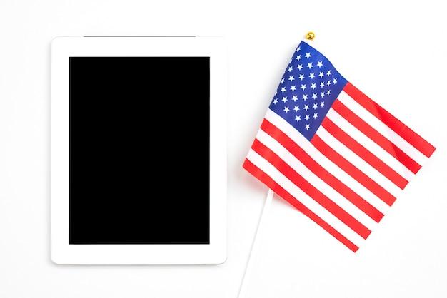 Tableta con pantalla en blanco junto a bandera americana.