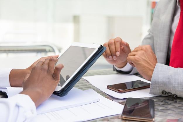 Tableta con pantalla en blanco en manos femeninas