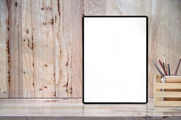 Tableta de la pantalla en blanco de la maqueta en la tabla de madera con el copyspace para la exhibición del producto.