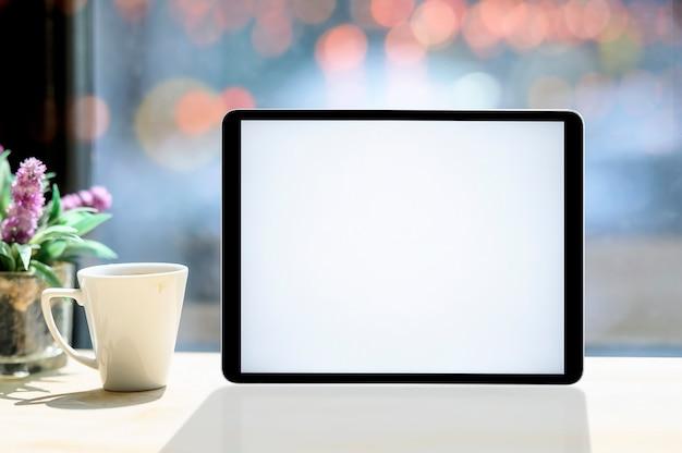 Tableta de la pantalla en blanco de la maqueta con la taza blanca en la mesa de madera blanca