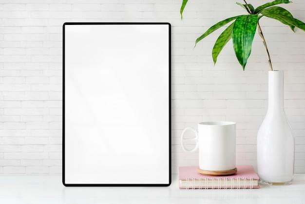 Tableta de la pantalla en blanco de la maqueta con la taza, el libro y el florero de la planta de interior en la tabla blanca