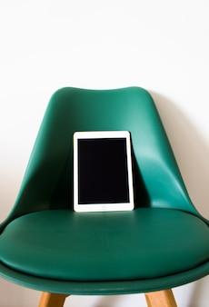 Tableta con pantalla en blanco en una silla