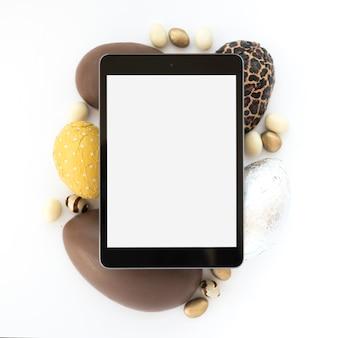 Tableta con pantalla en blanco sobre chocolate huevos de pascua