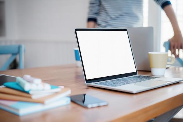 Tableta de pantalla de escritorio blanco en blanco con un hombre que trabaja en segundo plano