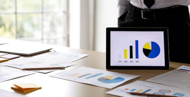 Tableta de pantalla táctil inalámbrica que muestra la presentación de información de diagrama de gráfico de tasa de crecimiento de ventas en el escritorio con documentos de papeleo. los empresarios preparan los datos de la estrategia de análisis para la gestión.