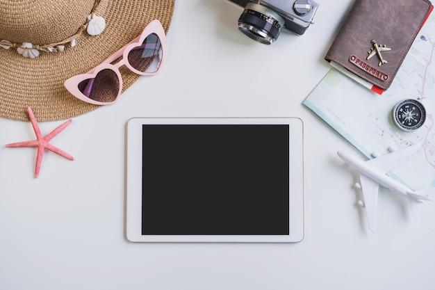 Tableta de pantalla vacía con accesorios de viaje y artículos sobre fondo blanco con espacio de copia, concepto de viaje