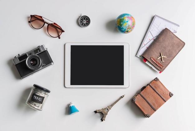Tableta de pantalla vacía con accesorios de viaje y artículos sobre fondo blanco