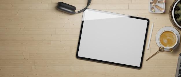 Tableta con pantalla vacía, auriculares, lápices de colores café y copie el espacio en la mesa de madera laicos plana