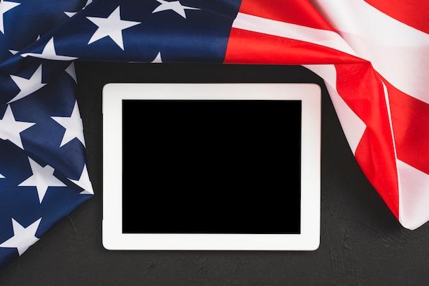 Tableta con pantalla vacía bordeando bandera americana