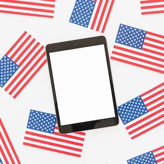 Tableta y pequeñas banderas nacionales de los estados unidos.