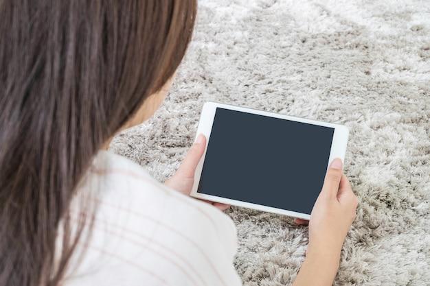 La tableta del primer en la mano asiática de la mujer en la alfombra gris borrosa texturizó el fondo con el espacio de la copia