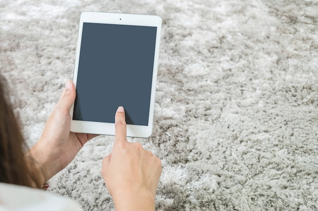 Tableta del primer en la mano de la mujer en fondo gris de piso de alfombra
