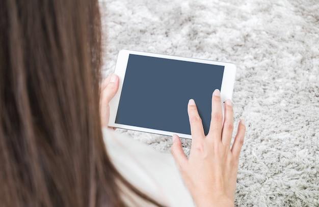 La tableta del primer en la mano de la mujer en piso de alfombra gris texturizó el fondo