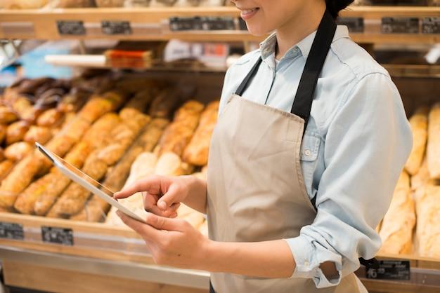 Tableta que practica surf sonriente del vendedor femenino de la panadería contra diversos pasteles
