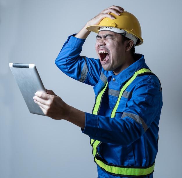Tableta que se sostiene estresante del ingeniero en fondo aislado mano. ingeniero con problemas en el trabajo