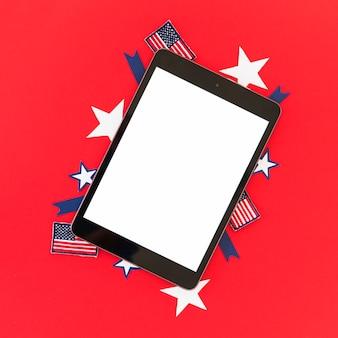 Tableta y símbolos de américa en superficie roja.