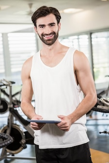 Tableta sonriente de la tenencia del hombre en el gimnasio