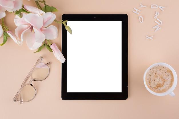 Tableta con taza de café y flores