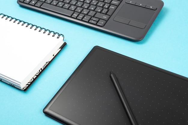 Tableta y teclado de gráficos en un fondo azul.