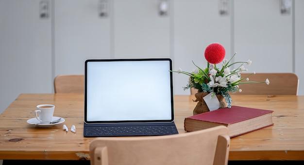 Tableta con teclado en mesa de madera en espacio de trabajo compartido, pantalla en blanco para diseño gráfico.