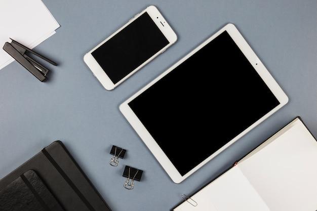 Tableta y teléfono inteligente con notebook en mesa gris