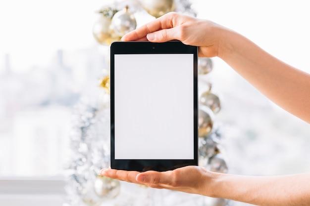 Tableta de la tenencia de la mujer cerca del árbol de navidad