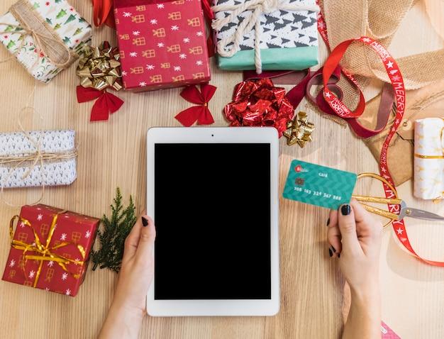 Tableta de la tenencia de la mujer y tarjeta de crédito en la tabla