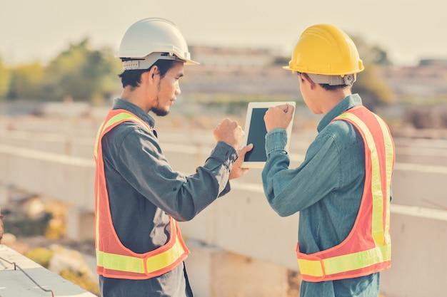 Tableta de uso de dos hombres de negocios en el proyecto de control de construcción del sitio edificio finca