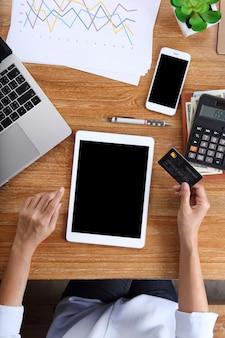 Tableta de uso de mujer de negocios con tarjeta de crédito, teléfono inteligente y papelería de oficina en escritorio de madera
