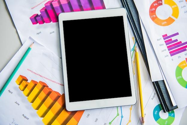 Tableta vacía sobre la mesa con gráfico de papel