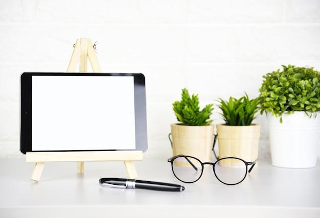 Tableta, vidrios y pluma de la pantalla en blanco en la tabla moderna en oficina.