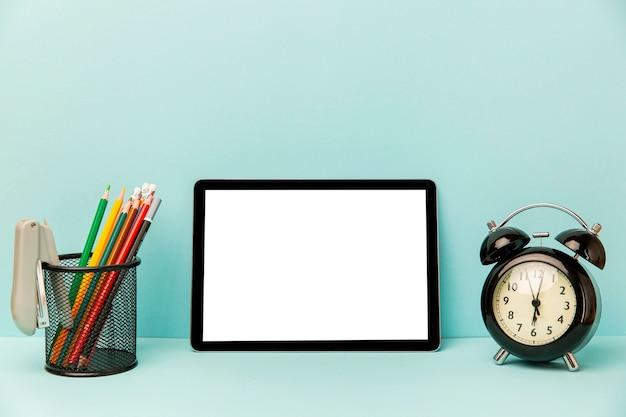 Tableta de vista frontal con reloj despertador sobre la mesa