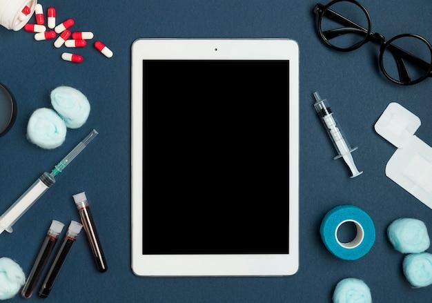 Tableta de vista superior rodeada de herramientas médicas