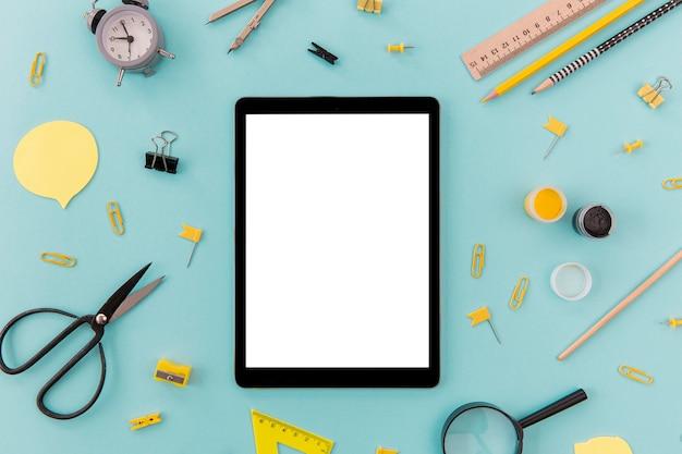 Tableta de vista superior rodeada de material de oficina