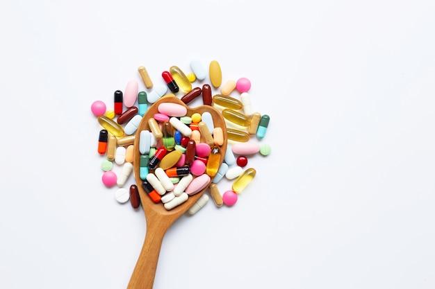 Tabletas coloridas con las cápsulas y las píldoras en blanco.
