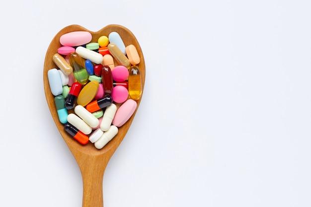 Tabletas coloridas con las cápsulas y las píldoras en el fondo blanco. cuchara de madera con forma de corazón.