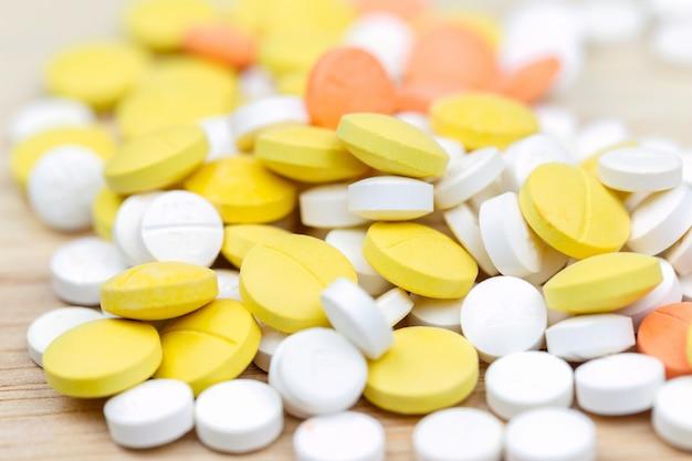 Tabletas coloridas de las píldoras de la medicina o primer de las drogas en el fondo de madera de la tabla.