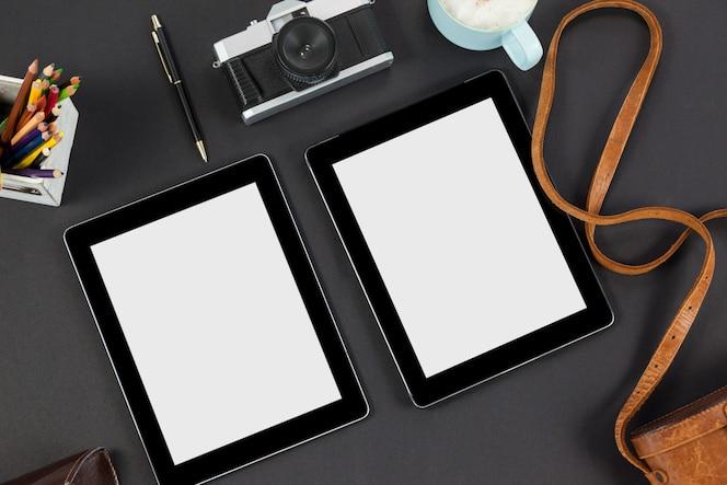 Tabletas digitales, lápices de colores, cámara, taza de café y bolígrafo.