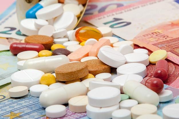 Las tabletas envueltas en euros con billetes en euros en un rosa. médico
