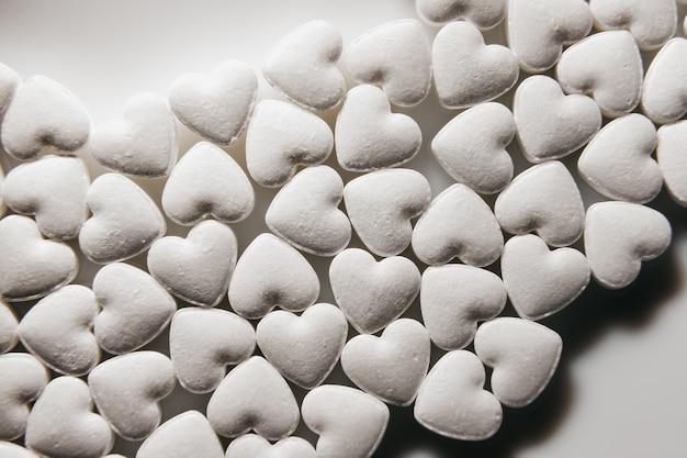 Tabletas golosinas. pastillas en forma de corazón. un montón de pequeños corazones.
