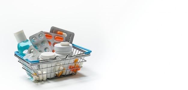 Tabletas y medicamentos en el carrito de compras sobre un fondo blanco. concepto de medicina y farmacia.