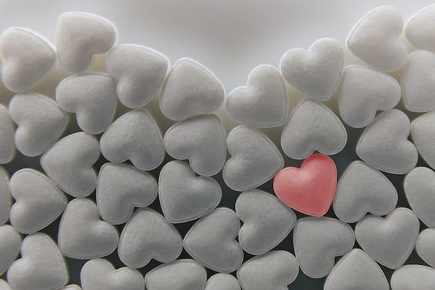 Tabletas pastillas en forma de corazón. un montón de pequeños corazones.