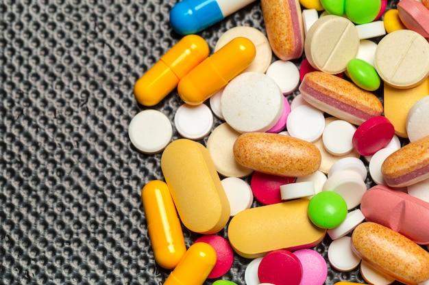 Tabletas y pastillas sobre fondo oscuro