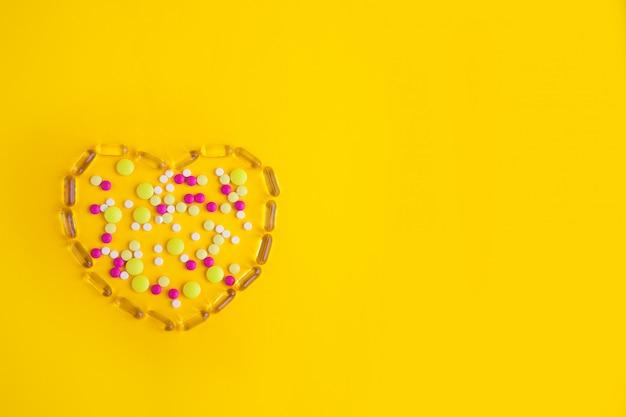 Tabletas, píldoras y cápsulas en forma de corazón.