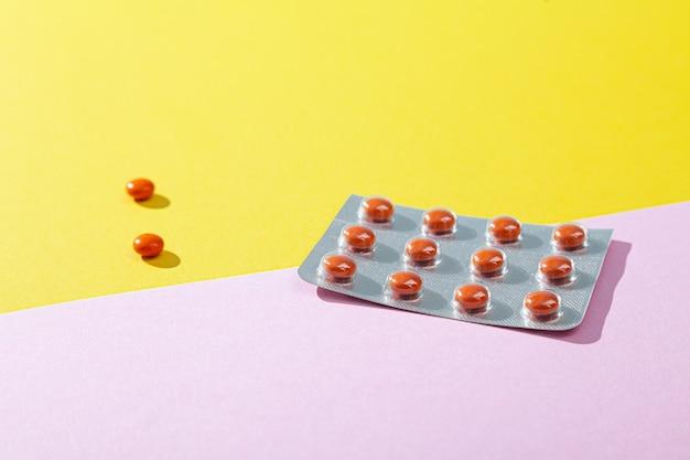 Tabletas y píldoras, vitaminas y antibióticos sobre fondo rosa, espacio de copia