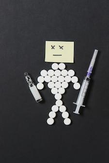 Tabletas redondas blancas de medicación dispuestas humano triste sobre fondo negro