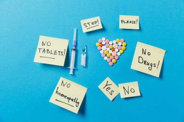 Tabletas redondas de colores de medicación en forma de corazón aislado sobre fondo azul.