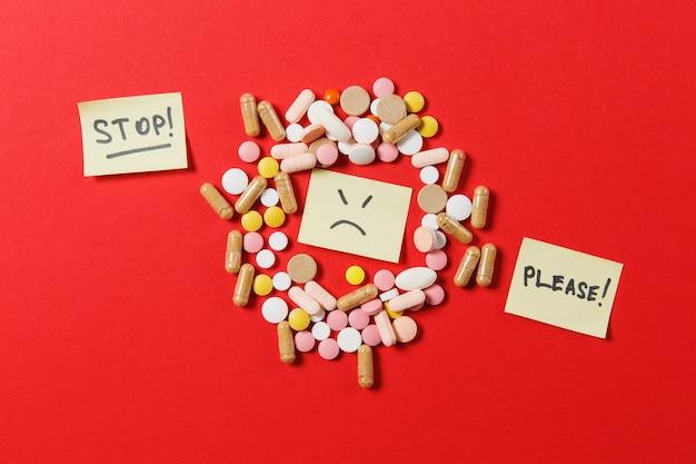 Tabletas redondas coloridas blancas de medicación dispuestas abstractas sobre fondo de color rojo