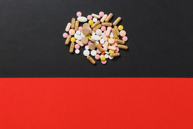Tabletas redondas coloridas blancas de medicación dispuestas abstractas sobre fondo negro rojo
