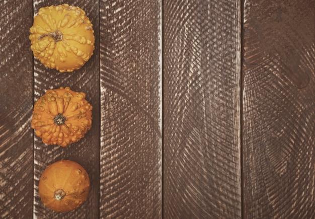 Tablón de madera y calabazas amarillas